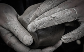 A Student shapes a piece of clay for the first time, connecting with the past through his hands.
