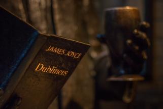 Joyce, still reading his book, in Temple Bar Dublin